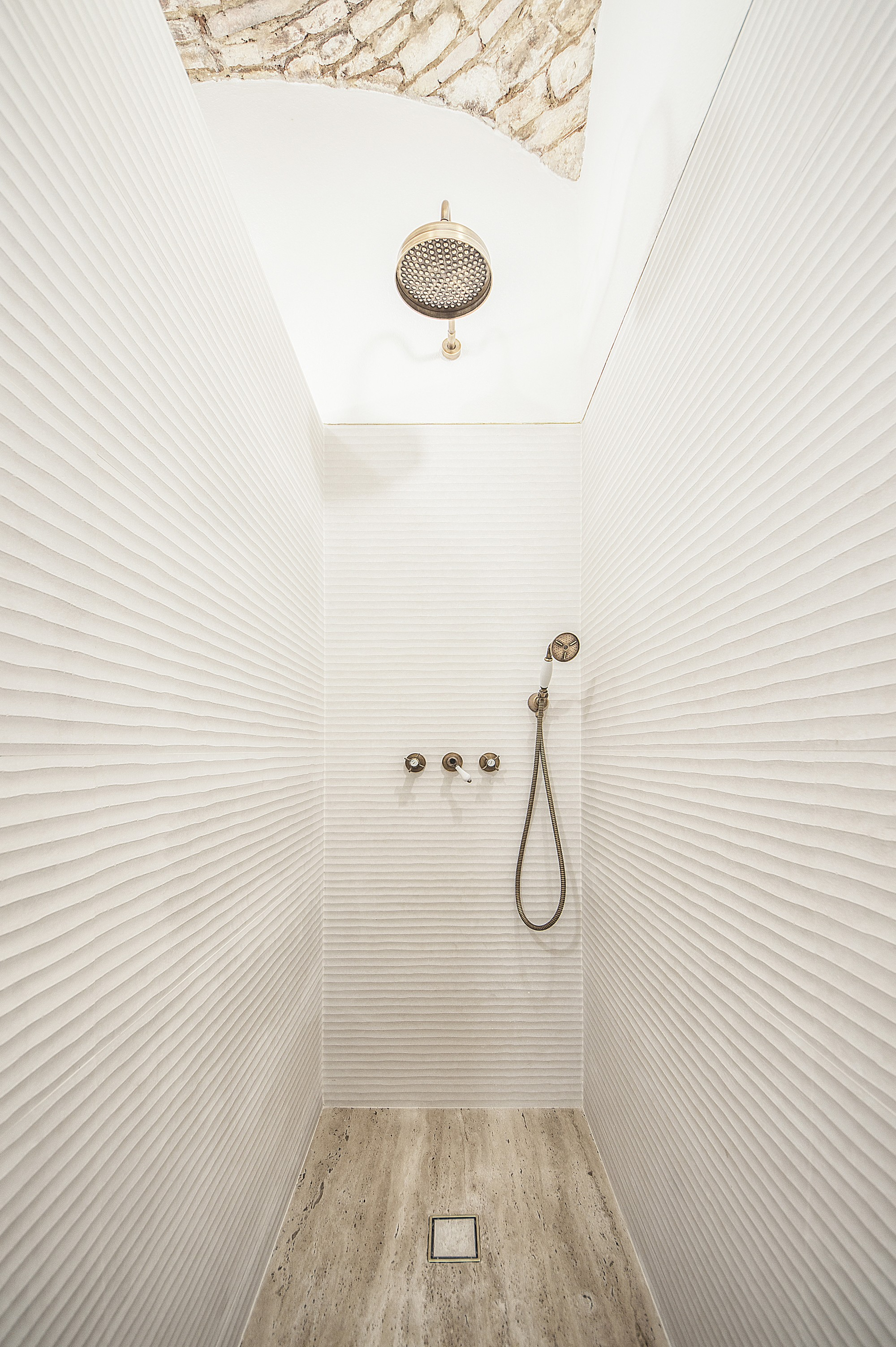 "Brushed brass ""rain shower"". Travetino stone base"